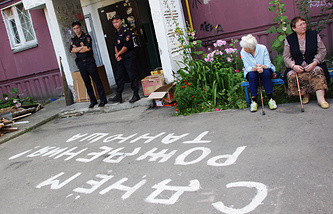 Police officers and neighbours outside a block of flats in Nizhny Novgorod, where six children were murdered