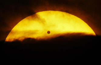 Venus seen passing in front of the sun in the clouds