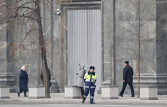 People pass by Federal Security Service building entrance hidden behind metal panels in Lubyanka square in Moscow