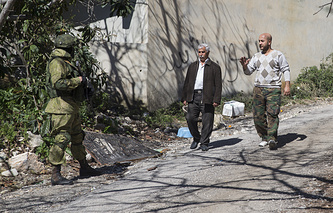 Locals greet a Russian soldier escorting the group of journalists to the village