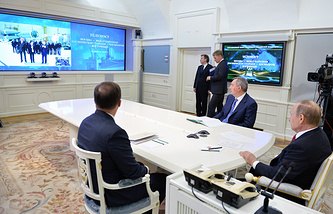 Russia's Deputy Prime Minister Dmitry Rogozin, Russia's President Vladimir Putin and Russian Federal Space Agency (Roscosmos) Head Igor Komarov during a video linkup with the International Space Station and the Vostochy cosmodrome