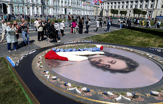 Tourists take pictures in front of the portrait of Peter the Grea in St. Petersburg