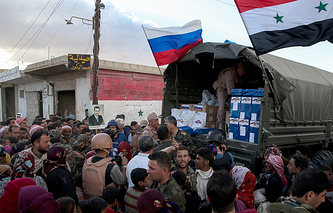 Syrian people receive Russian humanitarian aid in a camp near the town of Hama