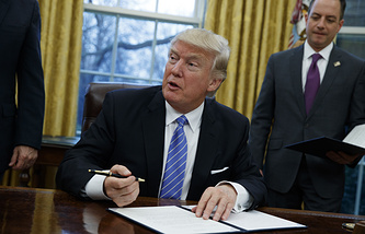 US President Donald Trump signs an executive order to withdraw the US from the Trans-Pacific Partnership trade pact