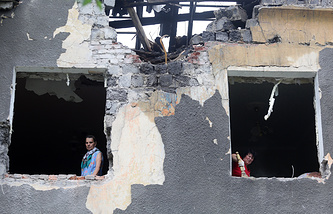 Local residents in a house damaged in a night shelling attack in Eastern Ukraine