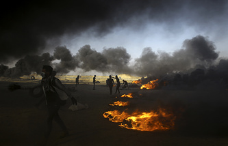 Palestinian protesters burn tires during a protest at the Gaza Strip's border with Israel