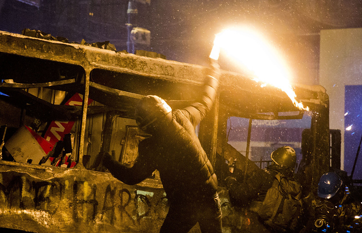 A protester throws a Molotov cocktail during clashes with police in central Kiev, Ukraine