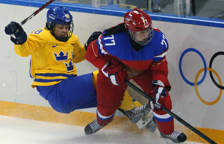 Inna Dyubanok (R) of Russia fights for the puck with Sweden player Anna Borgovist (L) during the match between Russia and Sweden
