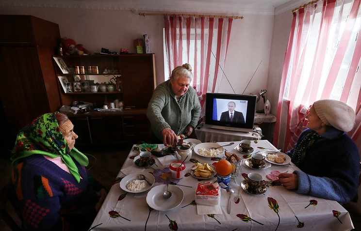 Women have their lunch as they watch Russian President Vladimir Putin on the television addressing the Russian Federal Assembly on the Crimean referendum to reunify with Russia outside Simferopol