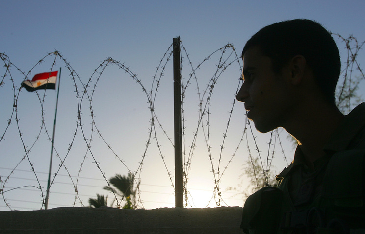 An Israeli soldier looks up at an Egyptian flag flying over the international boundary fence (archive)