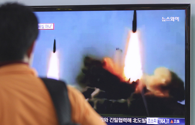A man watches a TV news program showing the missile launch conducted by North Korea, at Seoul Railway Station in Seoul, South Korea