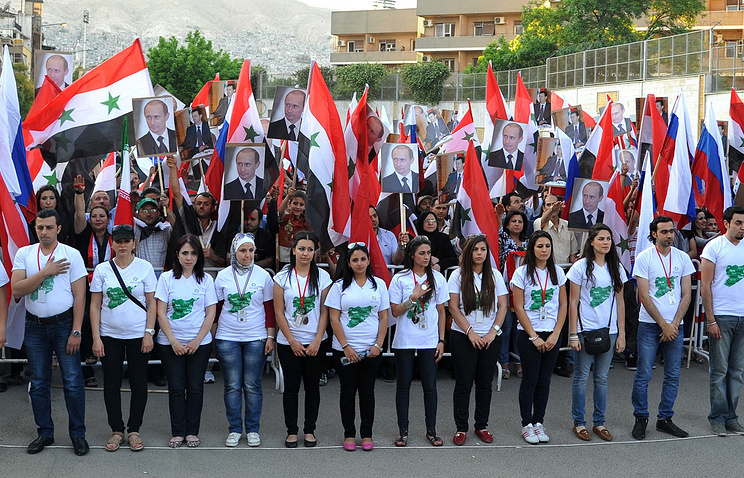 Syrian youths waving the Syrian and Russian flags with pictures of Russian President Vladimir Putin (archive)