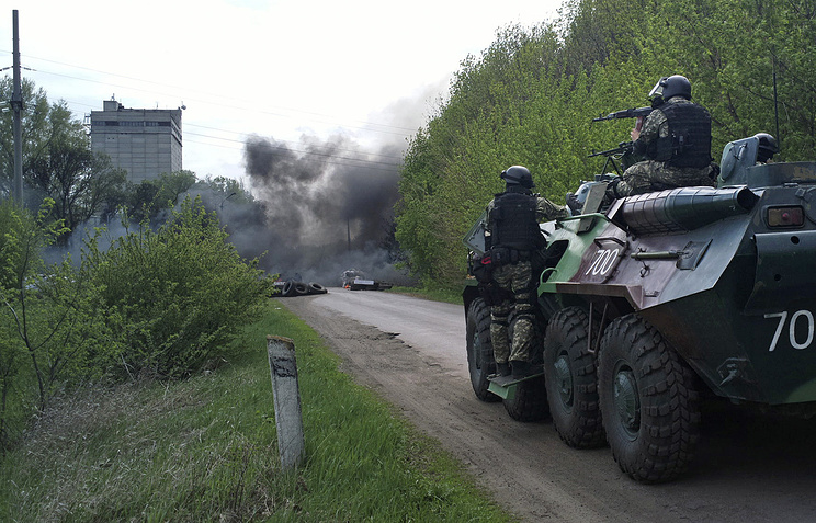 Ukrainian troops take position next to burning tires at a checkpoint following an attack by Ukrainian troops outside in Sloviansk