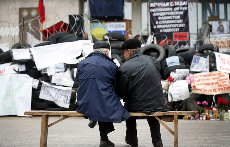 Two men sit in front of barricades in Donetsk