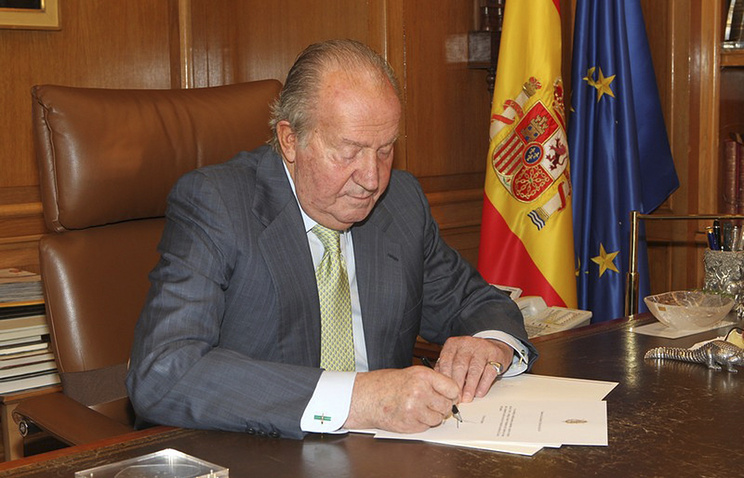Spain's King Juan Carlos signs a document in the Zarzuela Palace opening the way for his abdication
