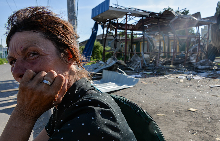A local woman sits near a building recentlly destroyed by Ukrainian Army