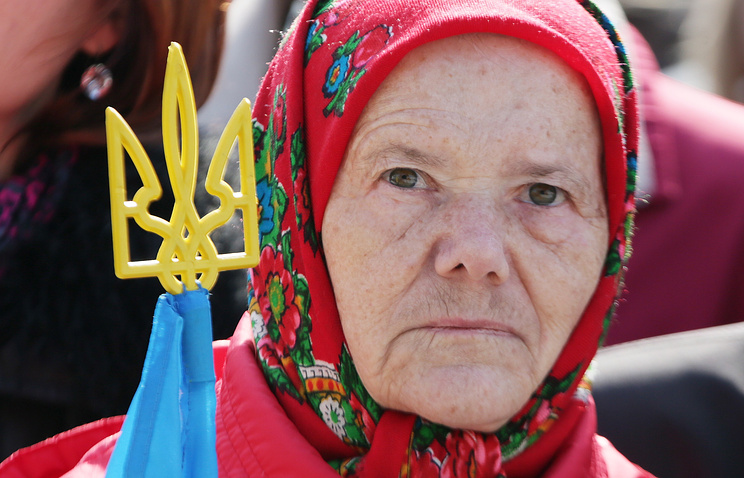 An aged woman with the Ukrainian coat of arms at a rally in Kiev (archive)