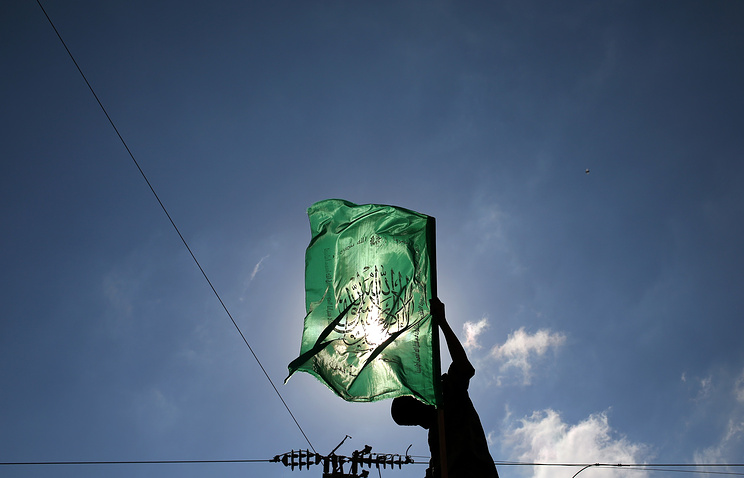 A Palestinian militant holds the Hamas flag