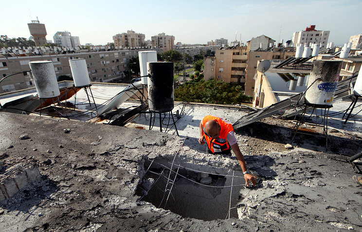 An Israeli security person assesses the damage on the roof of an apartment building in Ashkelon