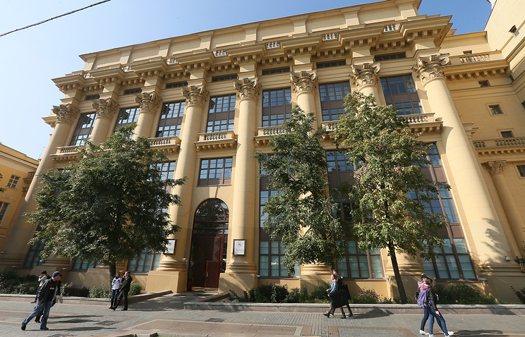 People pass the headquarters of Russian technology holding AFK Sistema in Moscow, Russia, 18 September 2014