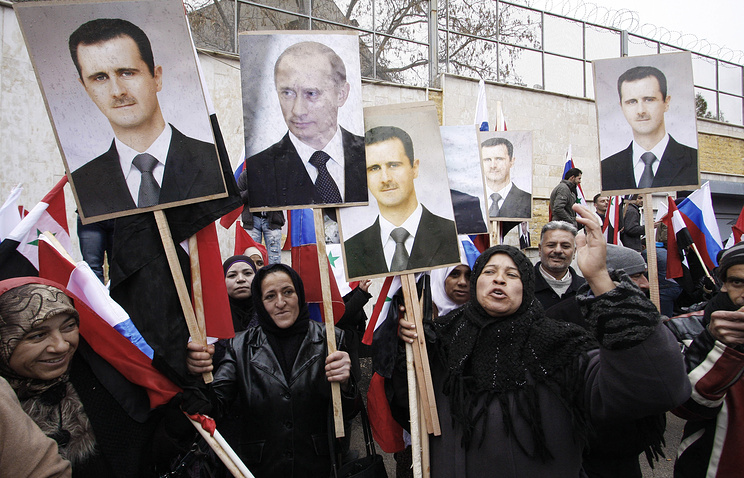 People hold photos of Syrian President Bashar Assad and Vladimir Putin during a rally in Damascus (archive)