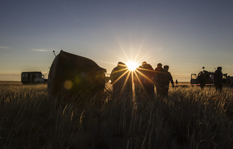Members of a search and rescue group seen after finding a descent capsule in Kazakhstan in 2013