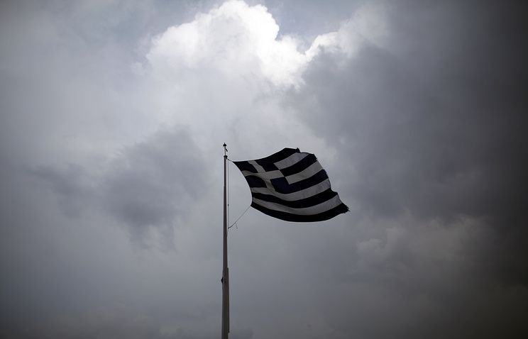 A Greek national flag flies on the mast atop the Acropolis hill