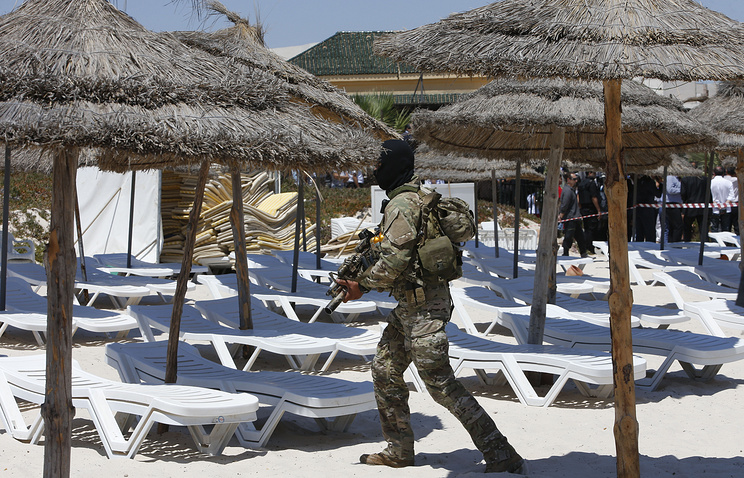 A hooded Tunisian police officer in front of the Imperial Marhaba hotel in the resort of Sousse