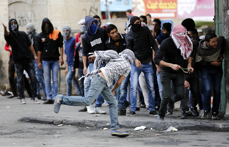 Palestinian protesters throwing stones at Israeli soldiers during clashes in the West Bank of Hebron