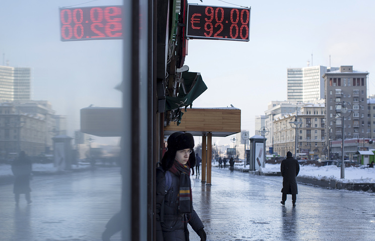 People walking past an exchange office screen showing the currency exchange rates of the Russian ruble, and euro in Moscow, Jan. 21, 2016