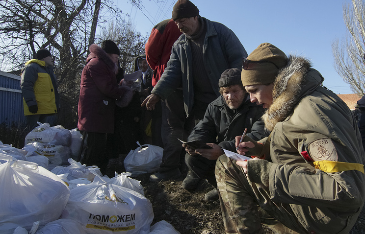 A Ukrainian volunteer battalion fighter distributes humanitarian aid among Shirokino residents, Feb 13 2015 (archive)
