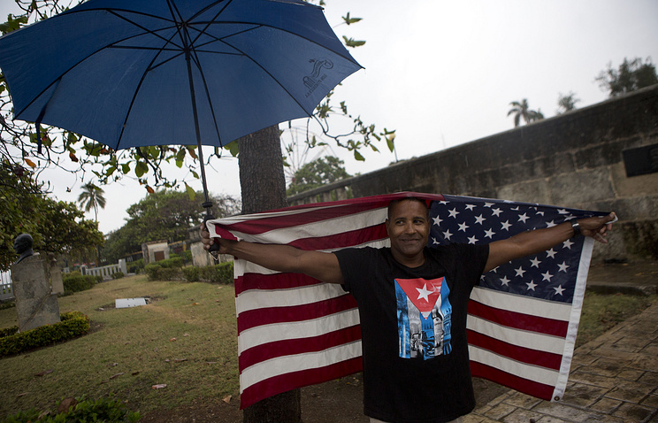 A Cuban man wearing a tee-shirt with a Cuban flag emblem and carrying flag of the US