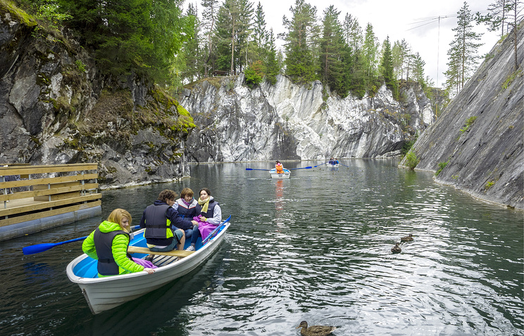 Tourists on a boat in an emerald lake in the Ruskeala Mountain Park, republic of Karelia, Russia