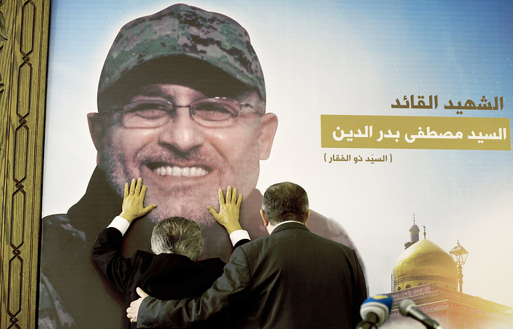 Adnan Badreddine (left), brother of top Hezbollah commander Mustafa Badreddine, grieves at his brother's picture in a southern suburb of Beirut, Lebanon