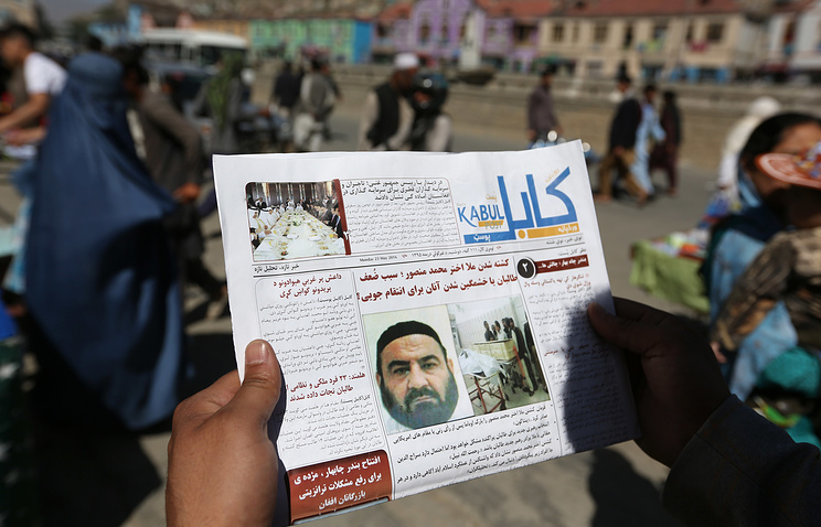A local newspaper with photos the former leader of the Afghan Taliban