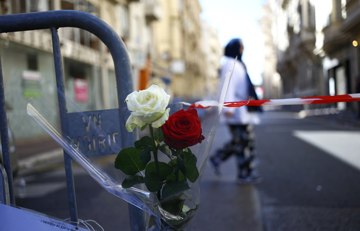 Flowers attached at a barrier near the scene after a truck attack in Nice