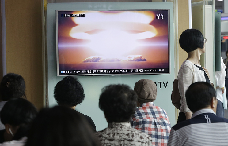 People watching a TV news program reporting North Korea's nuclear test