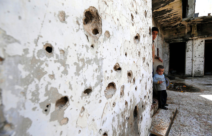 Syrian boys inside their destroyed house in Homs, Syria