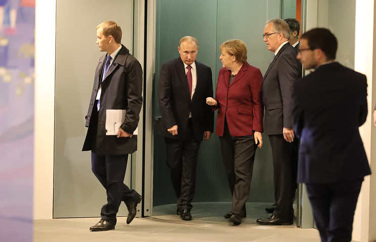 German chancellor Angela Merkel and Russia's president Vladimir Putin prior to talks with French president Francois Hollande and Ukraine's president Petro Poroshenko