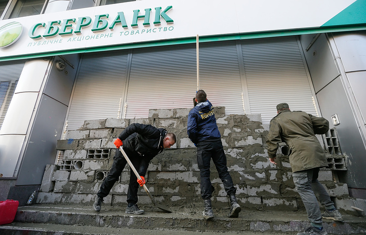 Activists build a wall to block entrance to the Sberbank of Russia office during a protest outside of a branch of Sberbank of Russia in Kiev, Ukraine