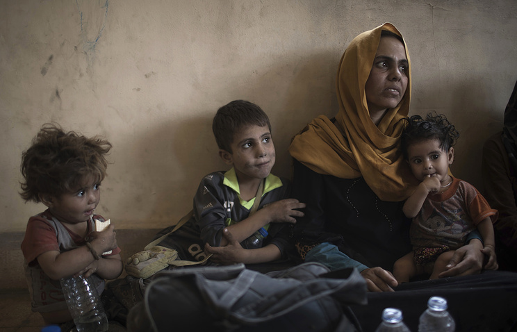 Iraqi civilians sit inside a house as they wait to be taken out of the Old City during fighting between Iraqi forces and Islamic State militants in Mosul