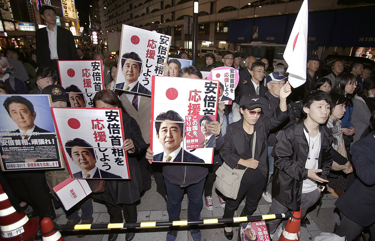 Supporters holding posters of Japan's Prime Minister and President of the ruling Liberal Democratic Party Shinzo Abe