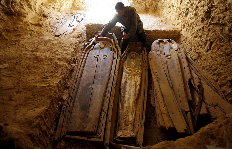 An Egyptian worker brushes dust off a wooden coffin containing mummy near the Illahun Pyramid in Faiyum, southwest of Cairo, 2009